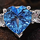 Electric blue topaz heart shape stone with side stone ring.